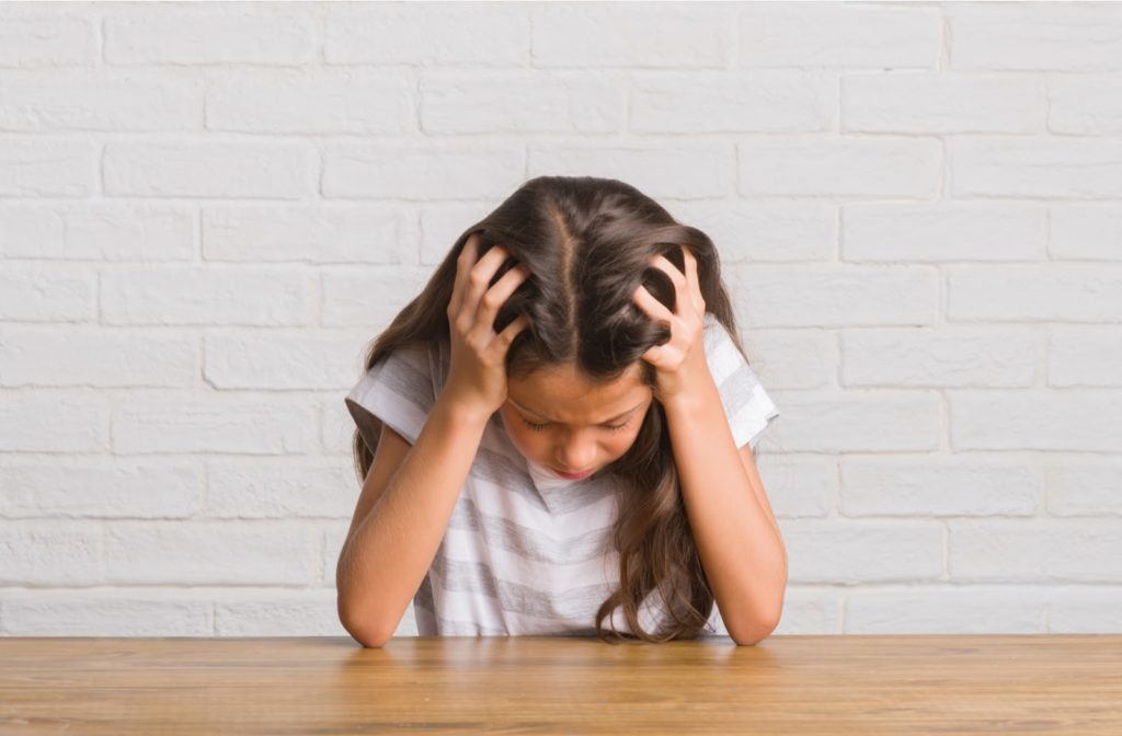 A young girl hunched over on a wooden desk holding her head because she has head pain due to impaired vision
