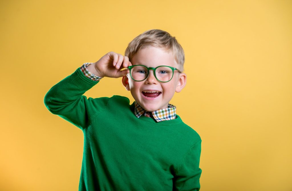 A little boy with a green shirt smiling while he is holding his green glasses on a yellow background