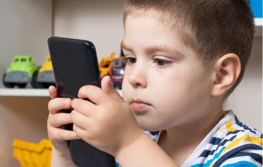 A young boy holding a phone very close to his face because of myopia (extreme nearsightedness)